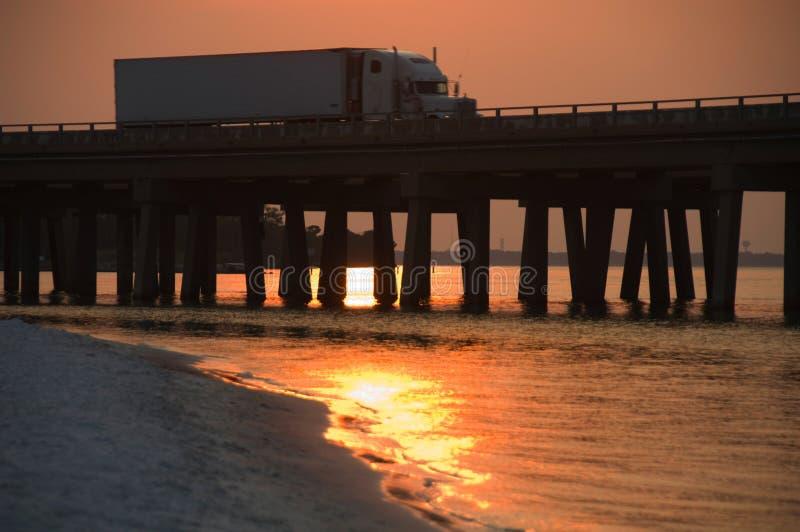 Truck crosses bridge in sunset stock photo