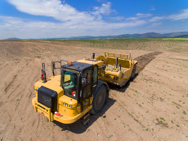 Truck cultivating ground. Modern vehicle cultivating ground in the summer time stock photography
