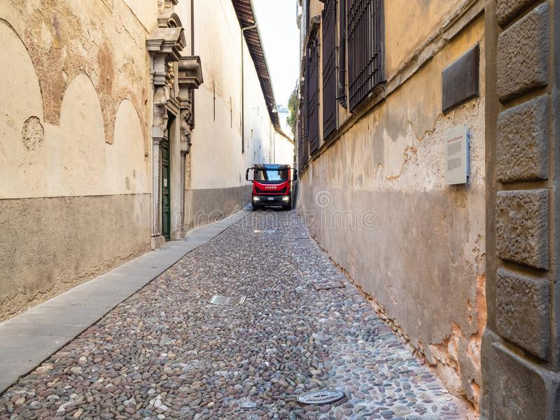 Truck drive on narrow medieval street in Bergamo stock photo