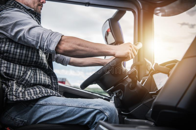 Truck Driver Behind the Wheel. Semi Truck Driving and Transportation Industry stock photos