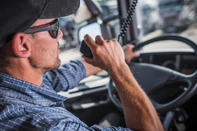 Truck Driver CB Talking. Caucasian Truck Driver in his 30s CB Talking with Other Drivers in the Convoy. Heavy Load Transportation Communication royalty free stock photo
