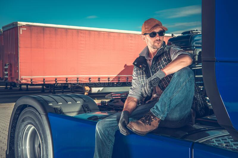 Truck Driver Chilling Out. Caucasian Truck Driver in His 30s Chilling Out on the Back of His Semi Tractor. Relaxing on the Truck Stop. Transportation Industry stock photo