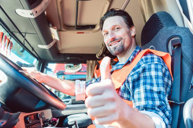 Truck driver sitting in cabin giving thumbs-up. Truck driver man sitting in cabin giving thumbs-up royalty free stock image