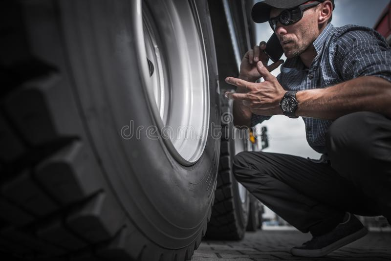 Truck Driver Ordering New Wheels. For His Semi Truck. Caucasian Worker Phone Conversation While Looking on the Rear Side of His Trailer Axle royalty free stock photos