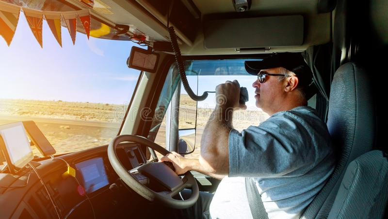 Truck drivers big truck right traffic hands holding radio and steering wheel. Truck drivers big truck right-hand traffic hands holding radio and steering wheel royalty free stock photo