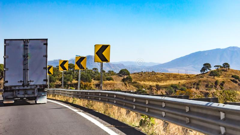 Truck driving on a road with dangerous curve signage. Wonderful sunny day to enjoy the scenery in the state of Jalisco Mexico stock photos