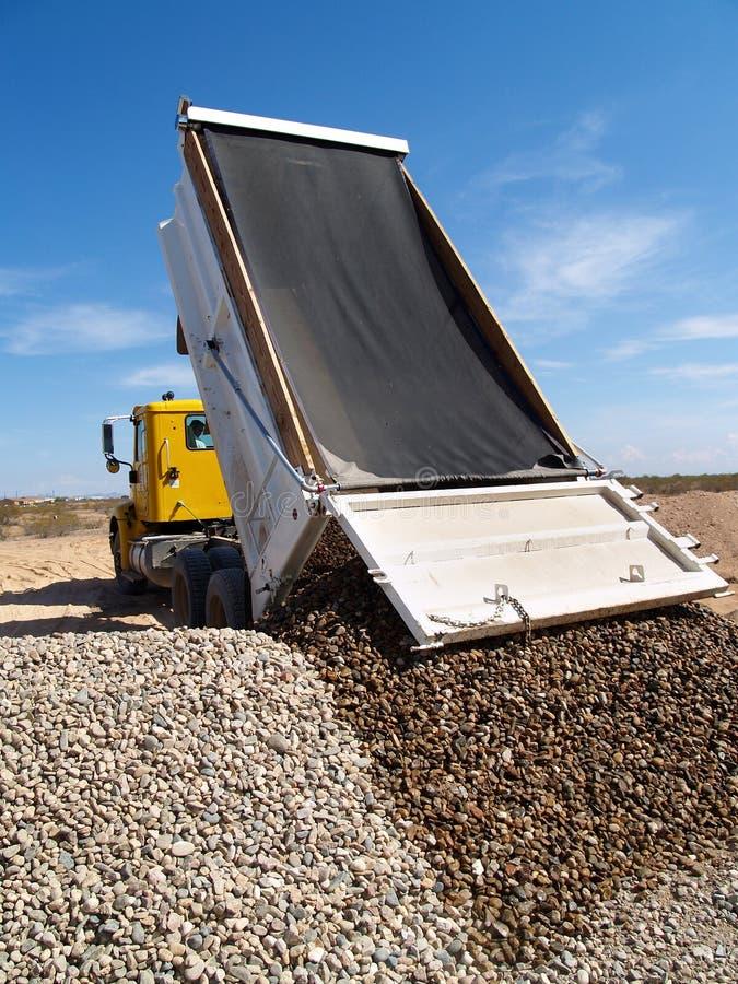 Truck Dumping Gravel. A dump truck is dumping gravel on an excavation site. Vertically framed shot stock image