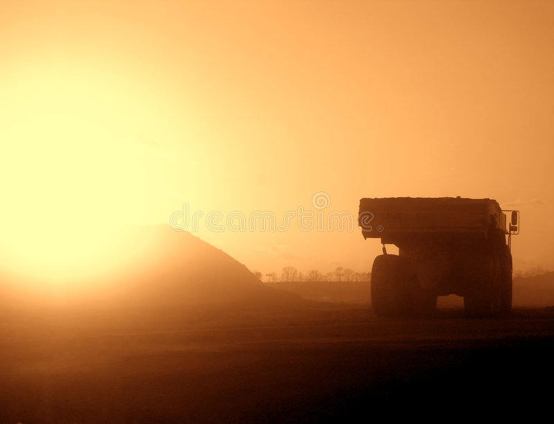 Truck on a Dusty Construction Site at Sunset. Heavy duty earth dirt hauler truck driving in dust cloud on a road construction site at sunset royalty free stock photo