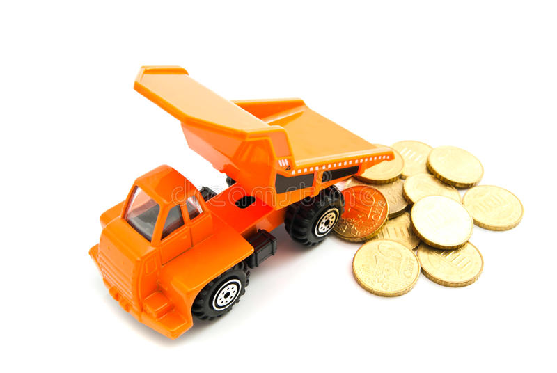 Truck and euro coins on white. Orange truck and euro coins on white closeup royalty free stock image