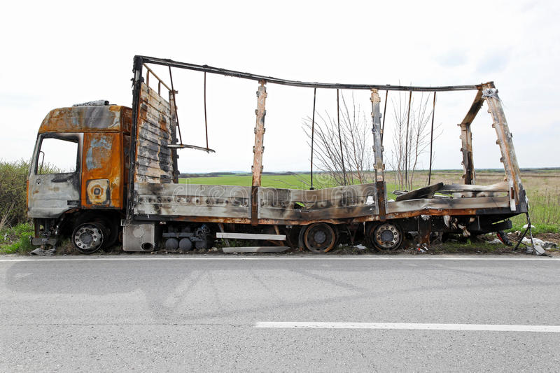 Truck after fire. Big truck destroyed in fire on side of the road stock image
