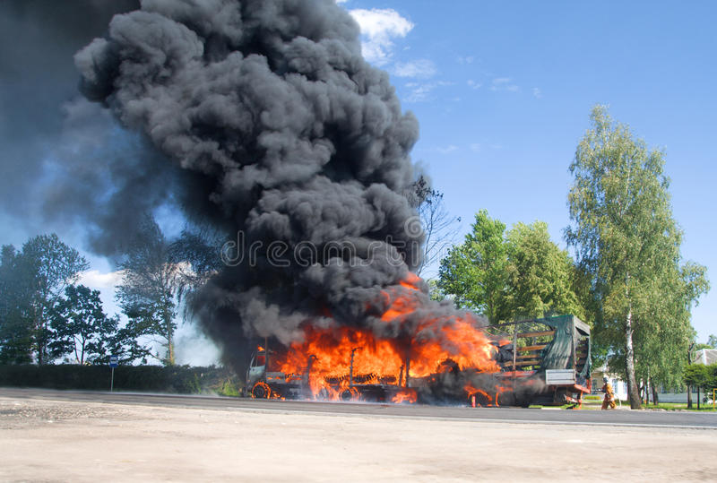 Truck in fire with black smoke on the road royalty free stock images