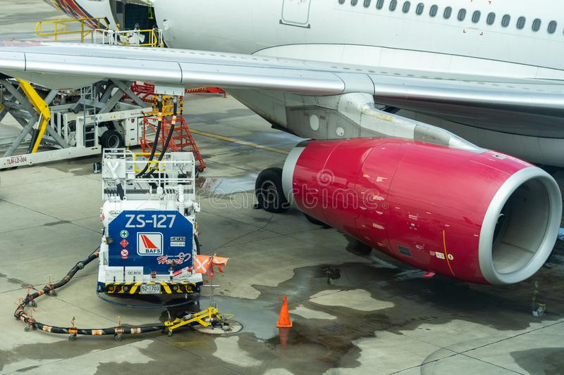 Truck with fuel tank on runway. Fuel truck refuel to the passenger plane. Workers Loading Bags Into plane. Oil truck stock images