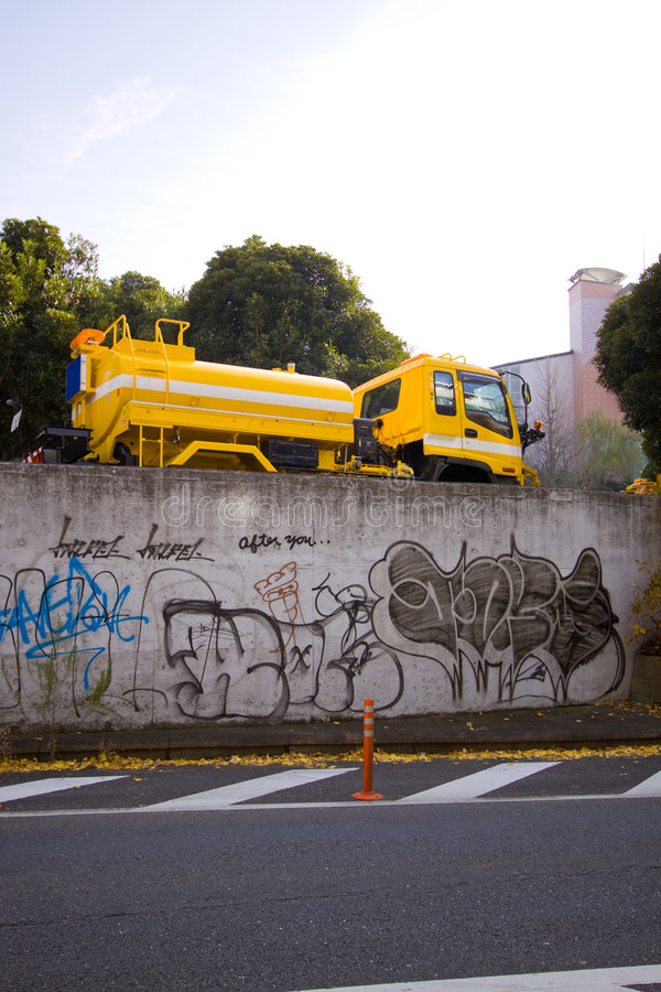 Truck & graffiti. A city maintenance truck on a roadside with graffiti written/painted on the wall below it in Tokyo, Japan royalty free stock photo