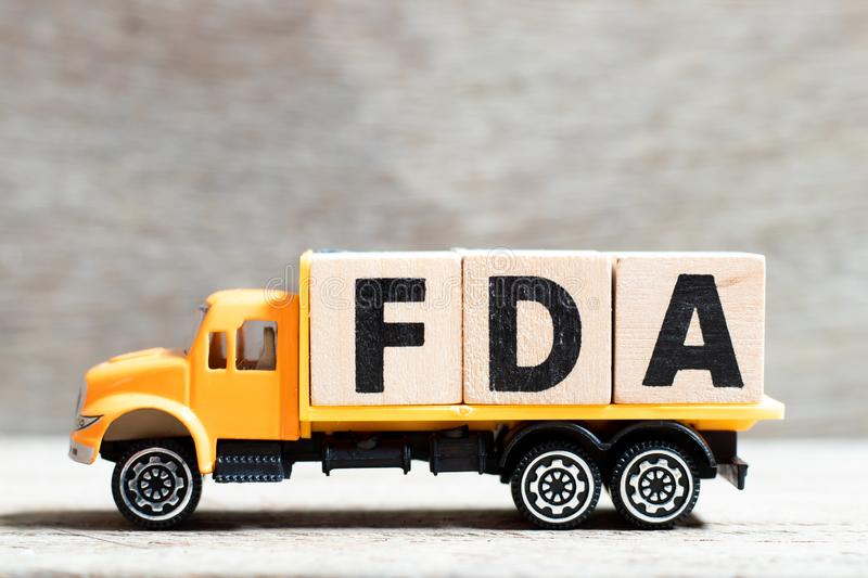 Truck hold letter block in word FDA abbreviation of food and drug administration on wood background. Truck hold block in word FDA abbreviation of food and drug stock photo