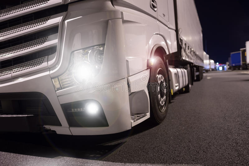 Truck with lights on at night. A truck with lights on at night royalty free stock photo