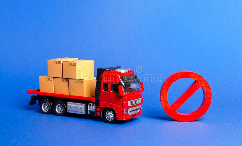 A truck loaded with boxes and a red prohibition symbol NO. Embargo trade wars. Restriction on importation, ban transit export dual. Use goods to countries under stock photo