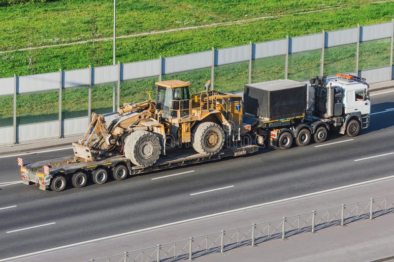 Truck with a long trailer platform for transporting heavy machinery, loaded big tractor with bucket. Highway stock images