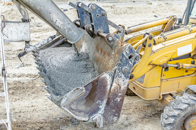 Truck mixer in process of pouring concrete into bulldozer scoop. Concrete mixer truck is pouring fresh concrete into excavator bucket at construction site stock photos
