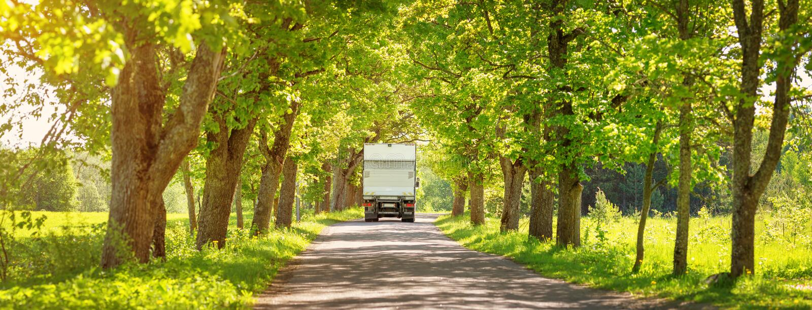 Truck moving on alley in summer. Lorry on asphalt road on spring day at park. Truck moving on alley in summer stock images