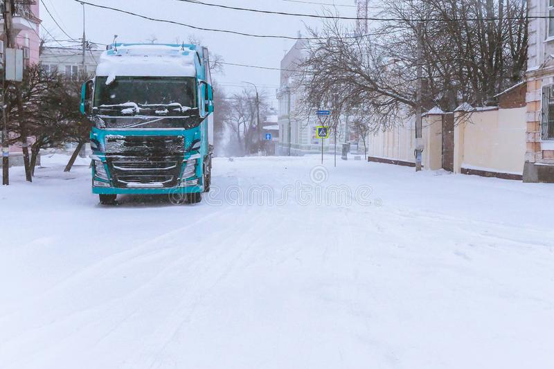 Truck parked in a city in a blizzard. Winter transportation of goods in the city. big truck covered with snow in the city royalty free stock image