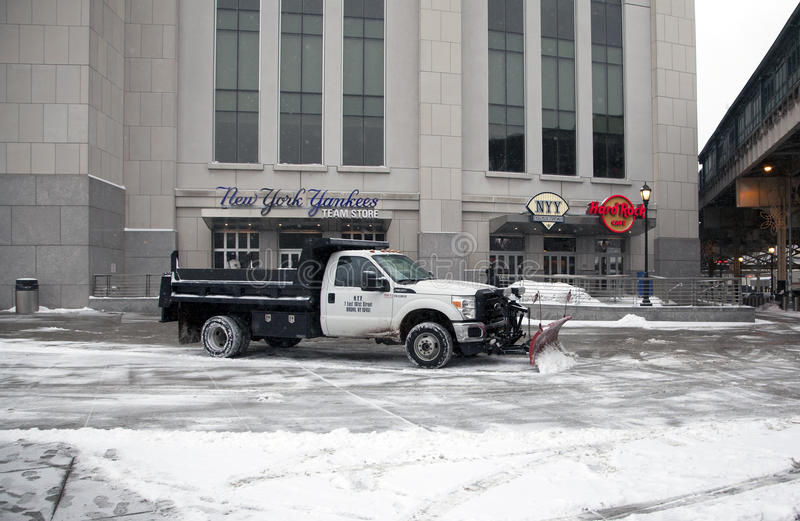 Truck with plow clears snow. BRONX, NEW YORK, USA - FEBRUARY 19: A truck with a plow clears snow in front of Yankee Stadium. Taken February 19, 2015 in the Bronx royalty free stock images