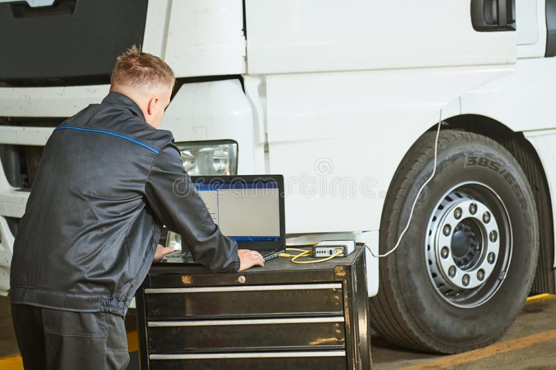 Truck repair service. Mechanic makes computer diagnostic of the semitruck. Truck repair. Mechanic perform computer electrical diagnostic testing and repair stock photography