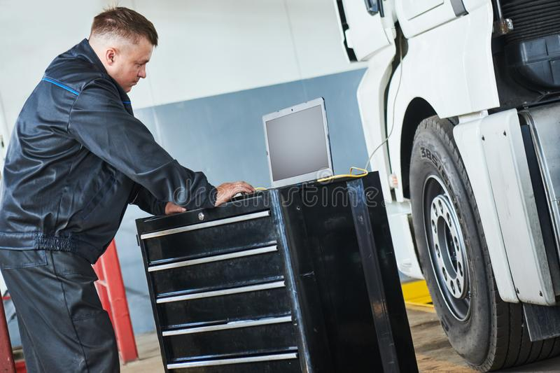 Truck repair service. Mechanic makes computer diagnostic of the semitruck. Truck repair. Mechanic perform computer electrical diagnostic testing and repair royalty free stock images