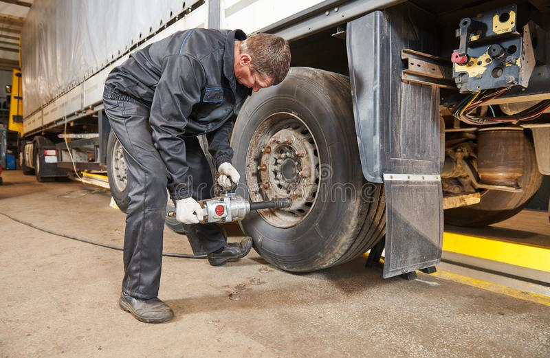 Truck repair service. Mechanic works with tire in truck workshop. Truck repair service. Mechanic takes off tyre for wheel replacement royalty free stock photography
