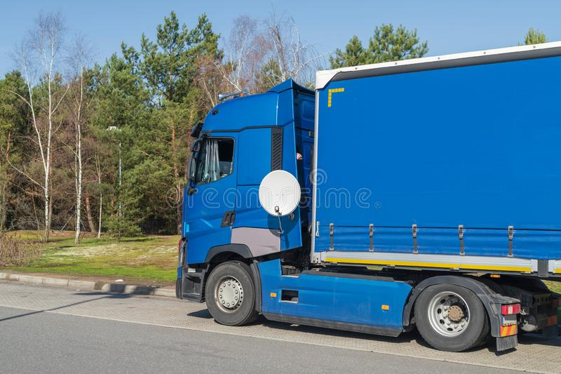 Truck at a rest area with a satellite dish. A blue truck has mounted a satellite dish for its longer break stock photos