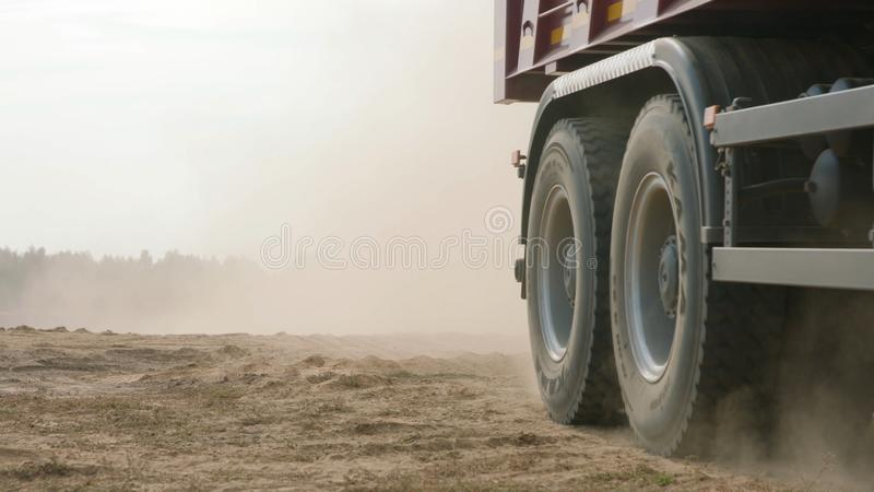 Truck rides on sand quarry road. Scene. Top view of dump truck driving on yellow dirt road in countryside. Large trucks royalty free stock photos