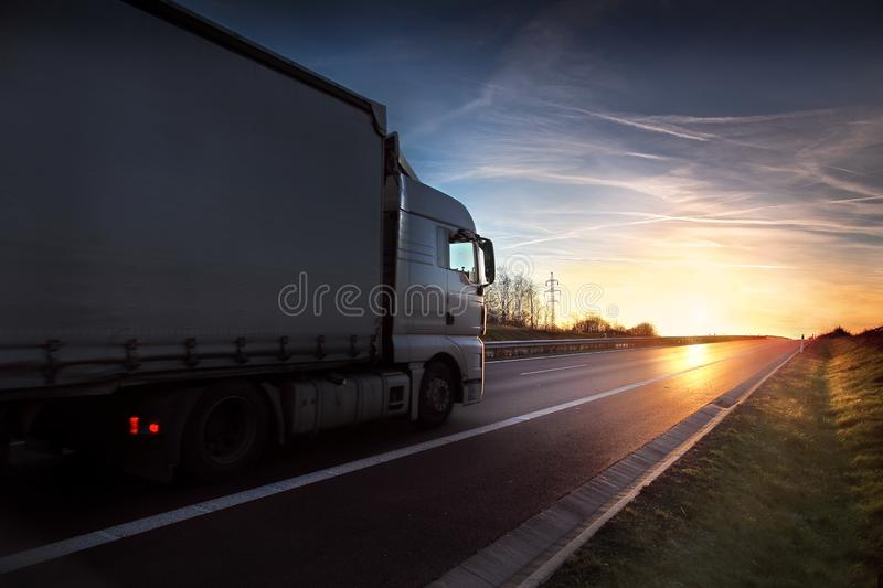 Truck on the road at sunset stock photo