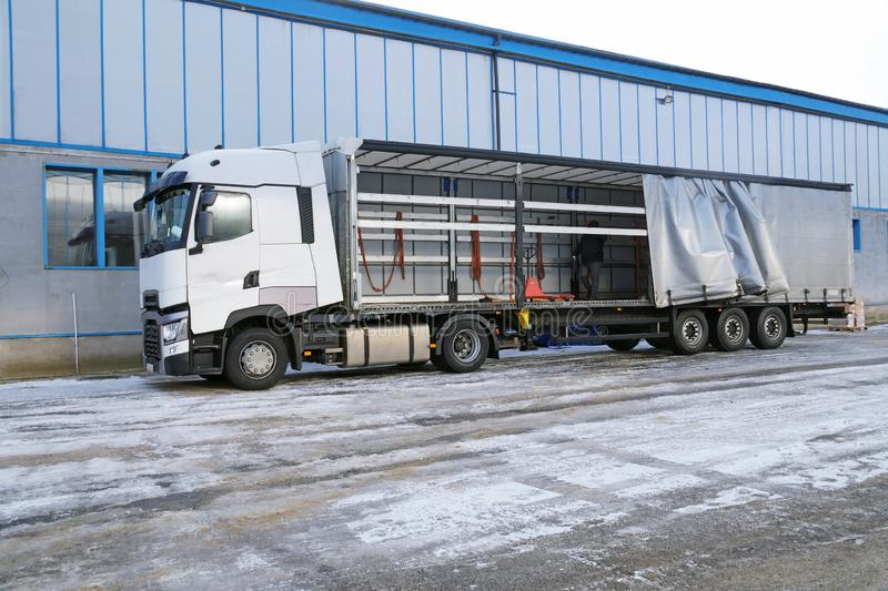 Truck and semi-trailer with an exposed tarpaulin during unloading. Transport and unloading stock image