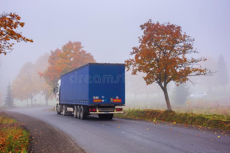 Truck on the serpentine in fog. Transcarpathia, ukraine - oct 09, 2018: truck on the serpentine in fog. breaking before the road turn. trees in fall foliage royalty free stock photography