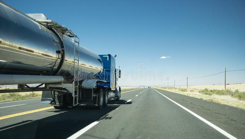 Truck with a silver tank trailer passing a passenger car on a highway. In Texas stock photos