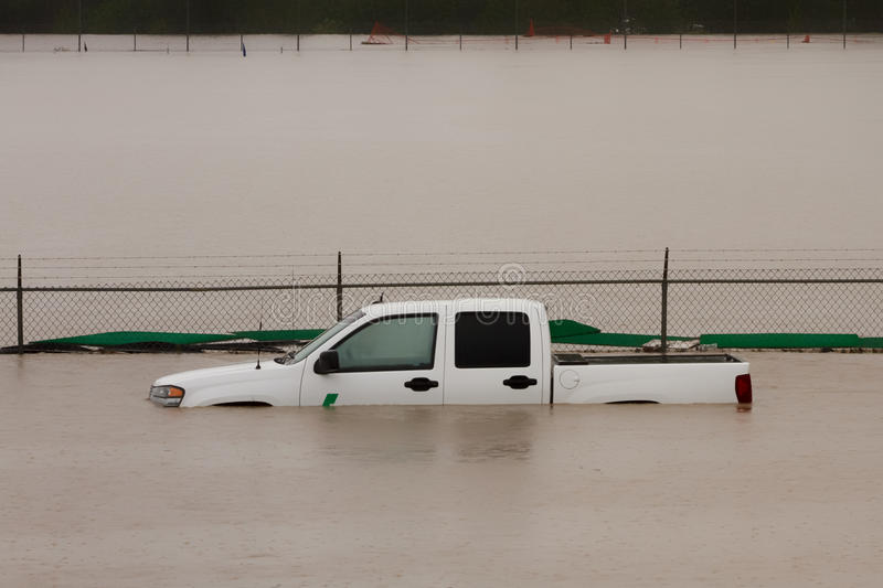 Truck Submerged in Flood Water. White truck submerged in flood water during the 2013 Calgary flood royalty free stock photos