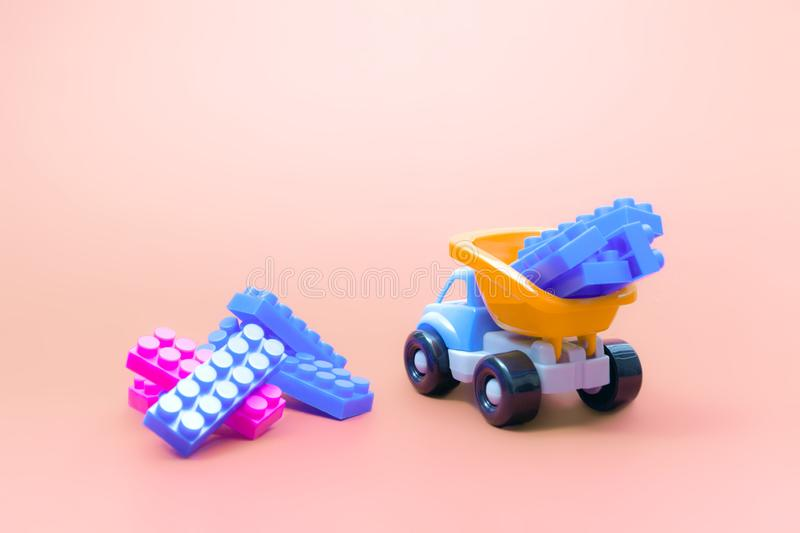 Truck toy model car with blocks of constructor on pink background stock photos