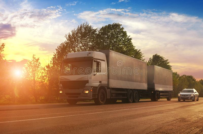 Truck with a trailer and other car on the countryside road against sky with sunset stock image