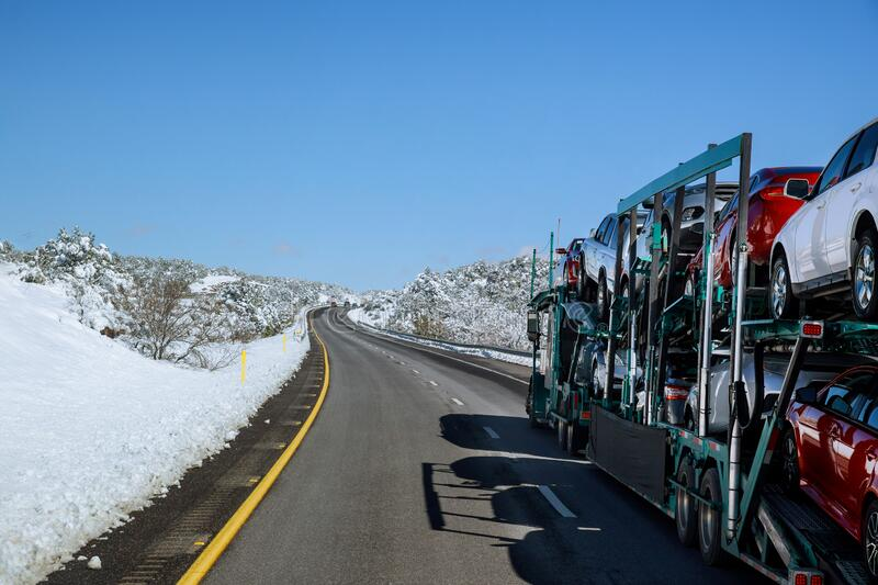Truck trailer transports new cars rides on highway road with snow covered landscape. In the mountains stock images