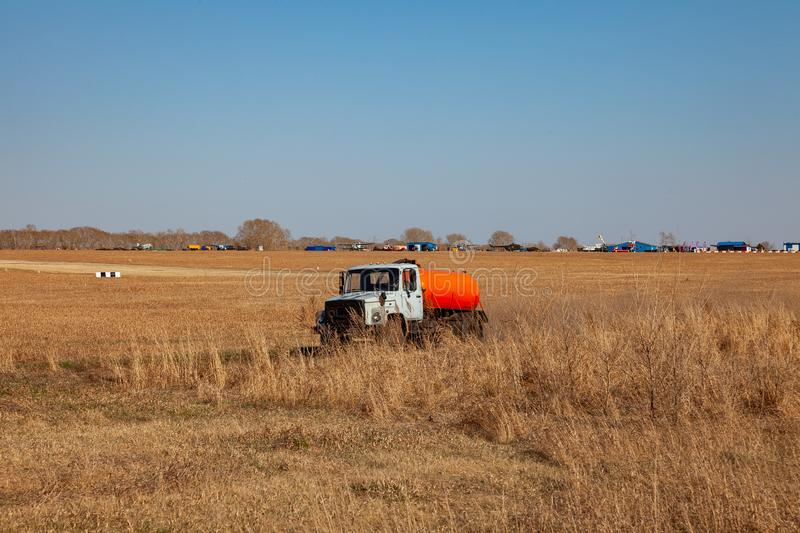 A truck for the transportation of gasoline and fuel with an orange tank rides in a yellow field on the road during the delivery of royalty free stock photo