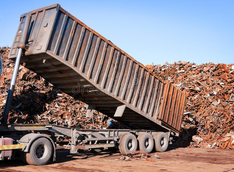Truck unloading metal scrap stock images