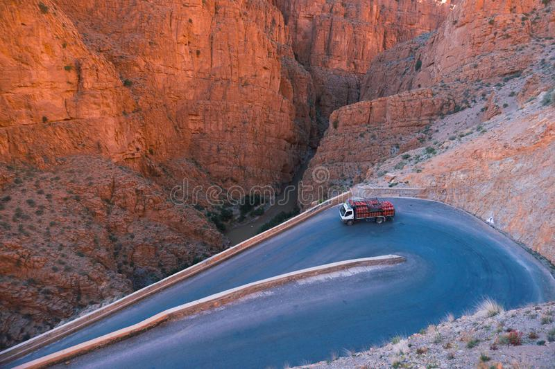Truck with usual for north Africa red gasbags on Serpentine mountain road in Gorges Dades in high Atlas, Morocco.  stock photography