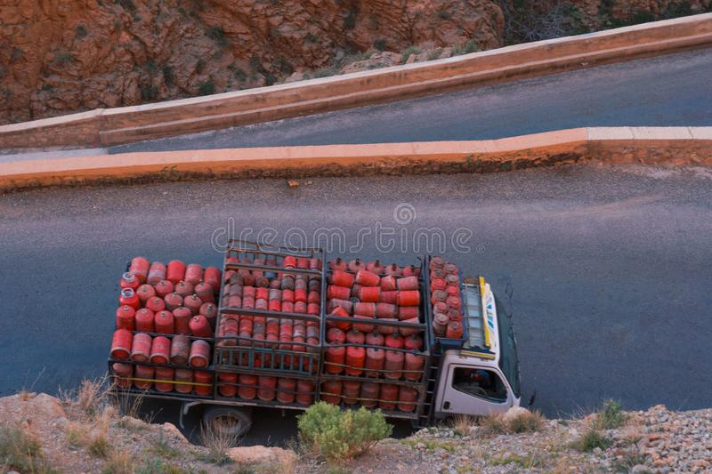 Truck with usual for north Africa red gasbags on Serpentine mountain road in Gorges Dades in high Atlas, Morocco.  stock photo