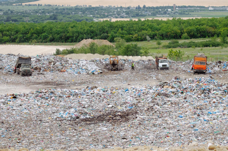 Truck working in landfill with birds looking for food. Garbage on the city dump. Soil pollution. Environmental protection. royalty free stock photo