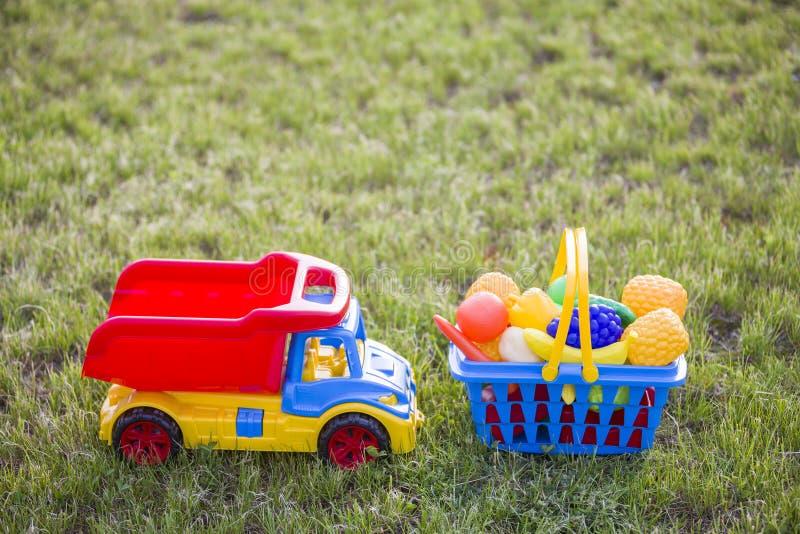 Truckand do carro uma cesta com frutas e legumes do brinquedo Brinquedos coloridos plásticos brilhantes para crianças fora no dia fotografia de stock royalty free