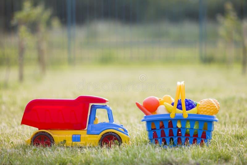 Truckand do carro uma cesta com frutas e legumes do brinquedo Brinquedos coloridos plásticos brilhantes para crianças fora no dia foto de stock royalty free