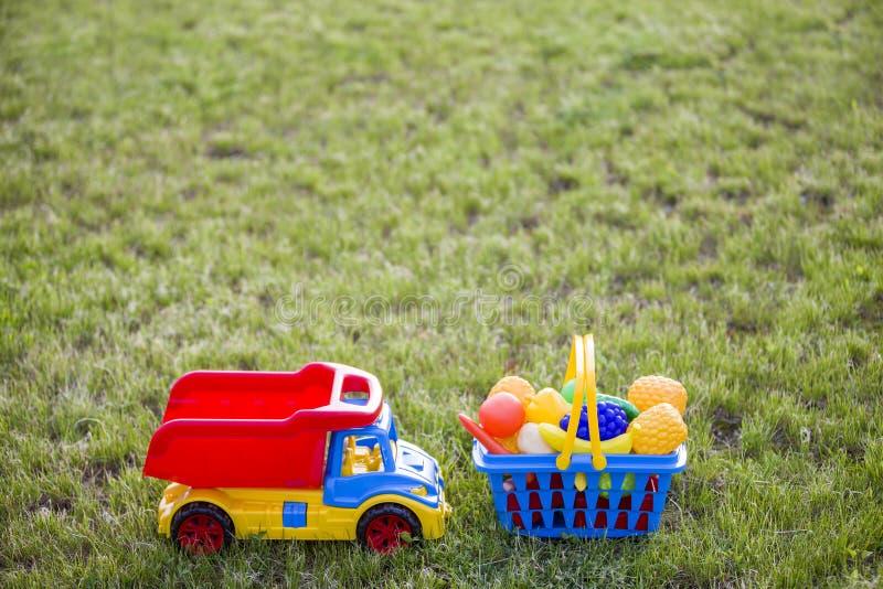 Truckand do carro uma cesta com frutas e legumes do brinquedo Brinquedos coloridos plásticos brilhantes para crianças fora no dia imagens de stock