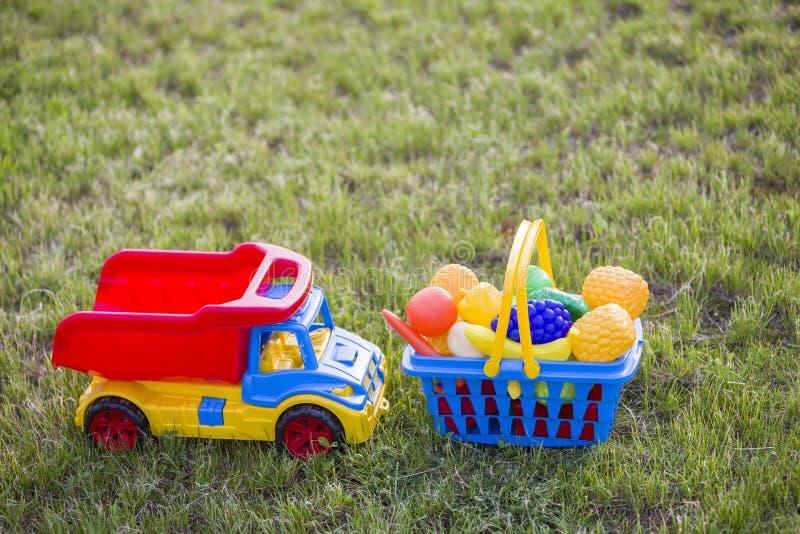 Truckand do carro uma cesta com frutas e legumes do brinquedo Brinquedos coloridos plásticos brilhantes para crianças fora no dia fotos de stock royalty free