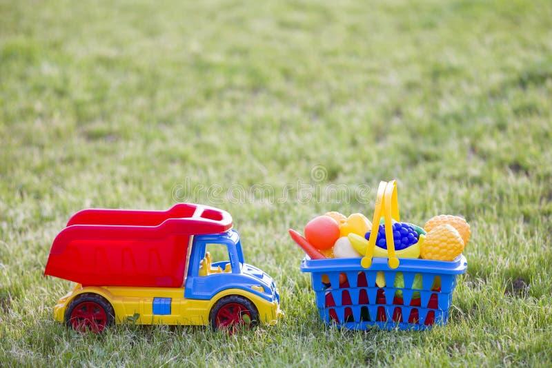 Truckand do carro uma cesta com frutas e legumes do brinquedo Brinquedos coloridos plásticos brilhantes para crianças fora no dia fotos de stock