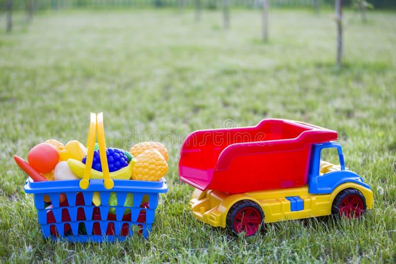 Truckand do carro uma cesta com frutas e legumes do brinquedo Brinquedos coloridos plásticos brilhantes para crianças fora no dia imagem de stock royalty free