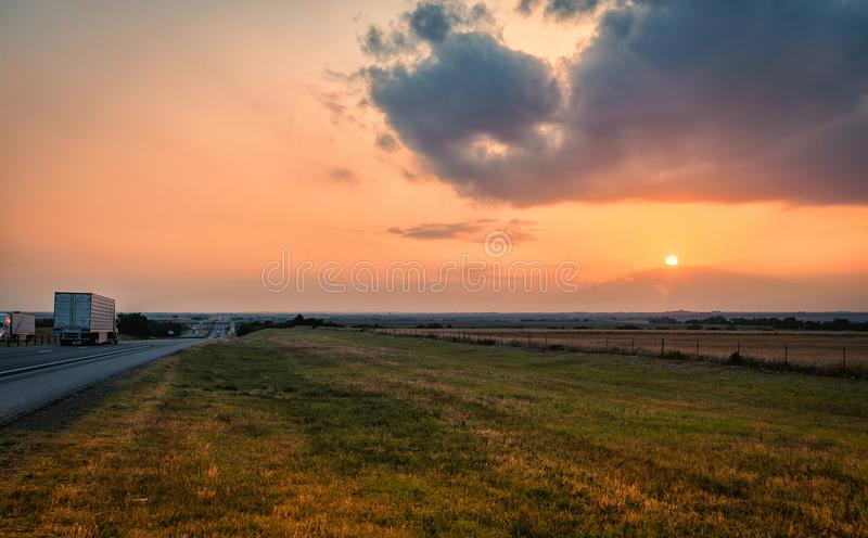 Trucks carrying cargo drive along interstate highway during Sunset over prairie land in oklahoma mid west america usa royalty free stock photos